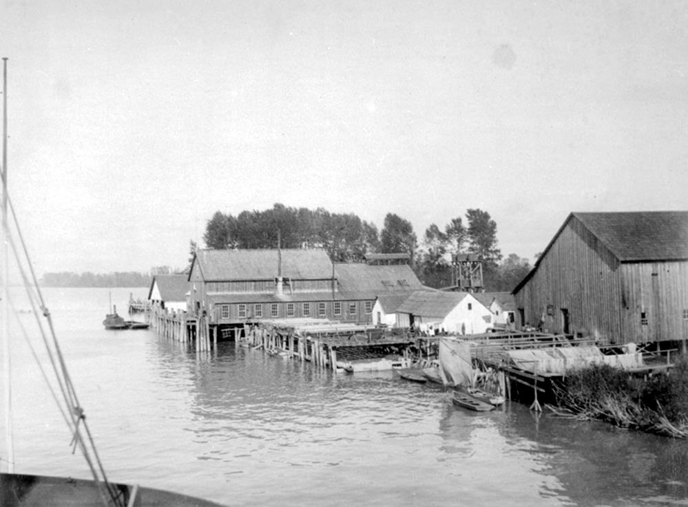 several wooden buildings of various sizes and heights at docks on a river bank