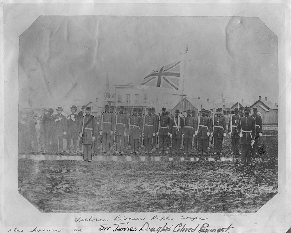 Une vingtaine de membres du « Pioneer Rifles Corp » de Victoria se tiennent debout en rangs avec le drapeau britannique en arrière-plan