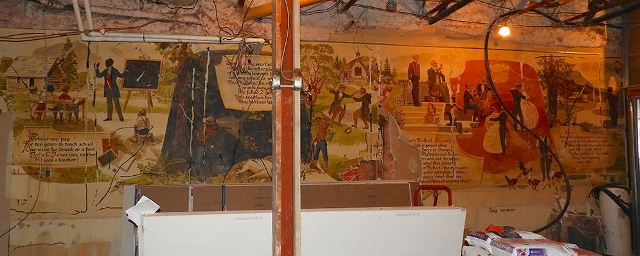 image of cracking walls of a wall mural; renovation and construction materials can be seen in the foreground