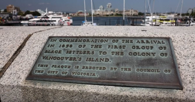 bronze plaque inlaid on top of a concrete causeway wall.