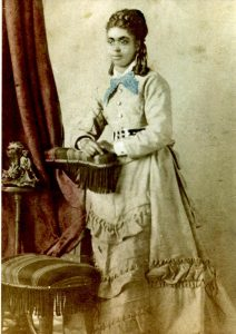 Hand tinted photo, young adult female standing next to a chair posing for the camera with a slight smile; wearing a long light-colored dress with wide belt, ruffles on the skirt. hair is in ringlets
