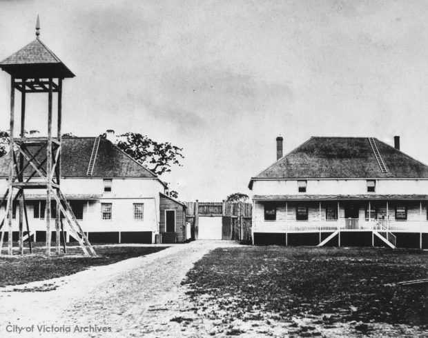 Black and white photo, a lookout tower stands before two large buildings. There is a gate between them with a pathway that goes between the buildings.