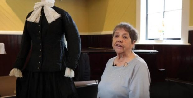 older woman sitting on piano bench in a church turned to the camera; mannequin with long black colonial dress to her right