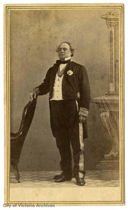 official professional portrait of older man standing, tuxedo, winged collar, medal on lapel