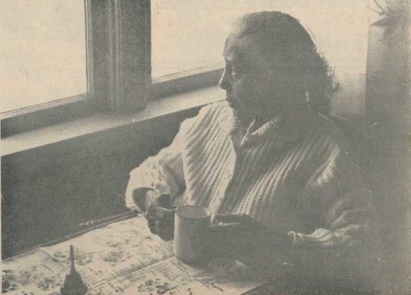 sepia photo, old woman seated at table with cup of tea and newspaper open on table, looking out a window
