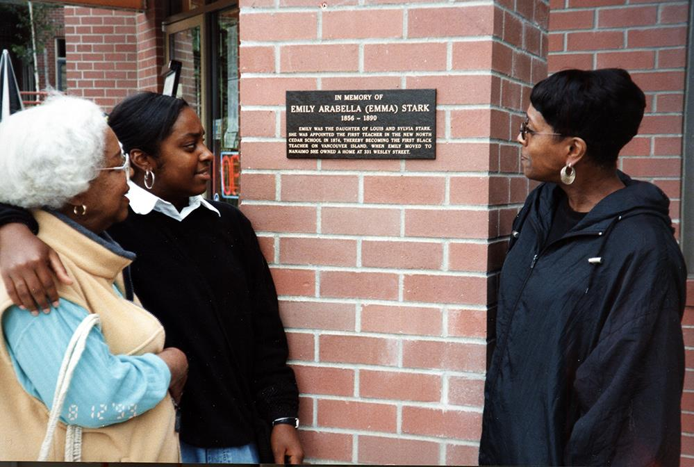 3 women of varying ages viewing a plaque mounted on a brick wall.