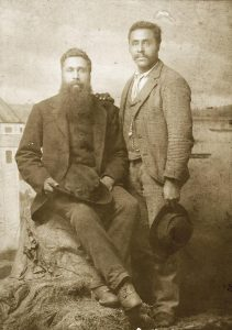 sepia toned photo, man seated on rock with full beard holding hat, man standing beside him, clean-shaven holding hat, seascape background