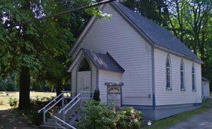 Église avec bardage à clin blanc et toit gris dans un décor boisé. Marches de l'entrée