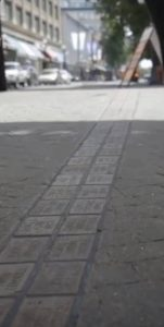 Square public montrant une double rangée de briques grises insérées dans le pavé où des noms y sont gravés
