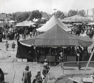 Black and white photo of crowds of people at a carnival midway with many tents set up and carousel in the background