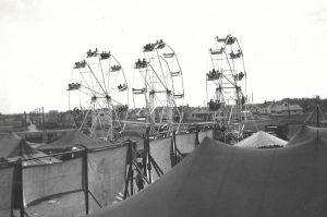 Black and white photo of carnival midway featuring people riding three Ferris wheels set up side by side among many tents and banners
