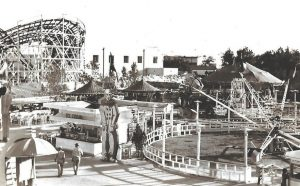 Black and white photo of carnival midway featuring a roller coaster, ice cream stand and up and down spinning thrill ride