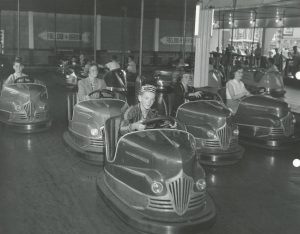 Black and white photo of people riding bumper cars featuring a young boy in front