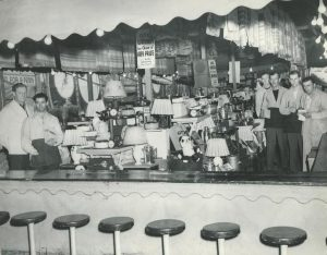 Black and white photo of people standing behind counter for game prizes with a sign that reads One Winner has Choice of Any Prize