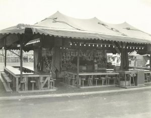 Black and white photo of carnival bingo game set up under a tent with many stools around tables, a wall of stuffed animal prizes and lights all around the top