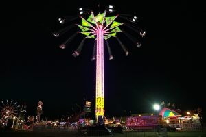 A very tall carnival ride in the middle of a midway, at the top are people swinging around in chairs attached by lines, the ride is lit up under the night sky