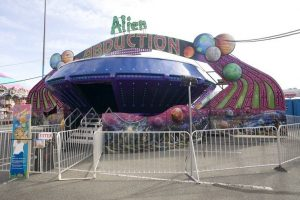 Alien Abduction carnival ride, the ride has a round shape with a big doorway to enter inside, there are colourful lights all over the outside and colourful graphics of outer space along the bottom, the WCA lion mascot is on a sign nearby