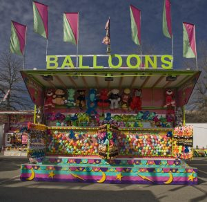 Carnival game concession stand, it is very colourful with flags at the very top, stuffed toys mounted on the wall, balloons for popping and canvas covering the bottom.