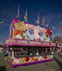 Concession food stand featuring cotton candy, also selling popcorn, candy apples, snow cones and cold drinks. The stand is pink and purple and has colourful graphics of the food all over