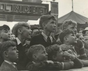 Black and white photo of a close up of young boys gathered together at the carnival, part of sign for thrill rides can be seen in the background