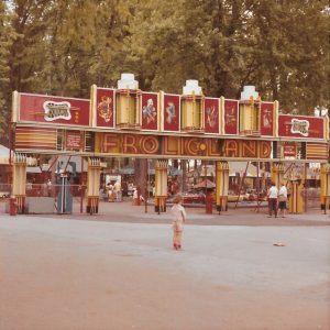 A small young girl stands in front of a large entrance to the carnival midway Frolic Land, there are not many other people around