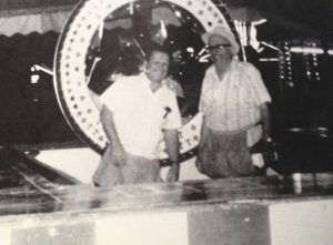 Black and white photo of a middle aged Bingo Hauser smiling and wearing a microphone headset standing beside another man, both behind a carnival game counter and larger spinning wheel is behind them