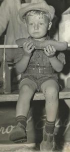 Black and white photo of a small young boy holding a foot-long hot dog, sitting with a bottle of soda beside him