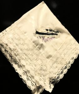 An off-white folded handkerchief with lace edging, there is embroidery in the middle in black and letters in purple