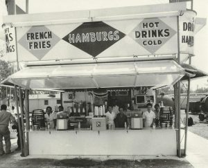 Black and white photo of a food concession stand, the sign says French Fries, Hamburgs and Hot Cold drinks, there are employees behind the counter with some in an all white uniform