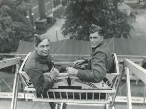 Black and white photo of two male soldiers in uniform riding a Ferris wheel, RCA is visible on one of the men's jackets
