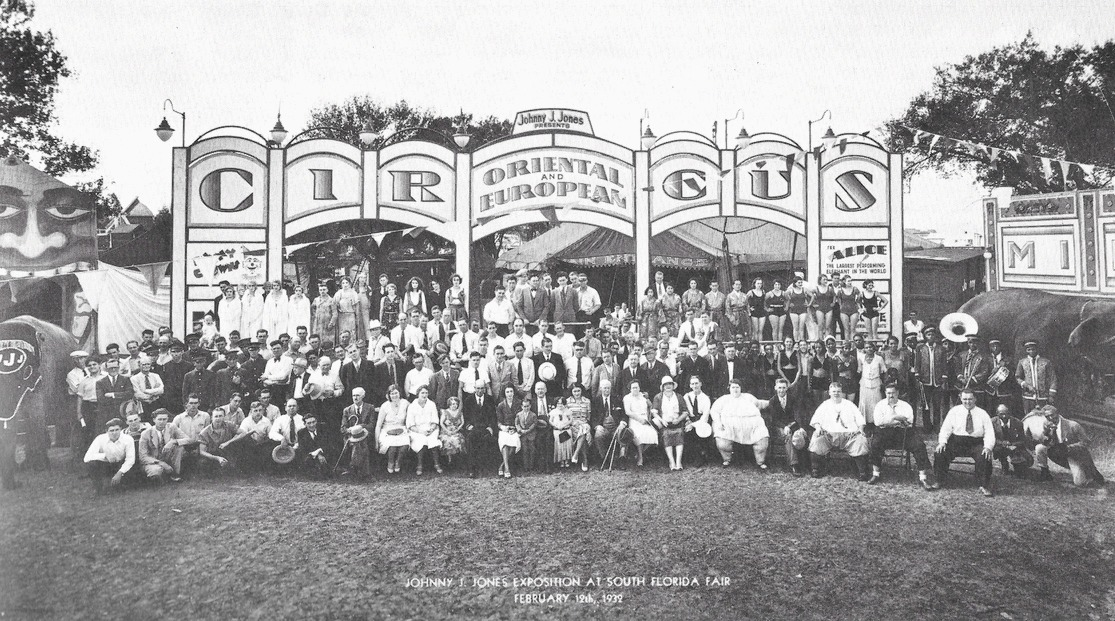 Black and white group photo of many people with a circus, visible is a very obese woman, a band, people in costumes, women in bathing suits and large cut boards with the circus title and one of a painted face with a large open mouth