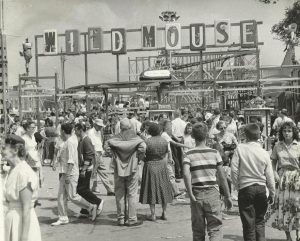 Black and white photo of a crowded carnival midway featuring the Wild Mouse roller coaster