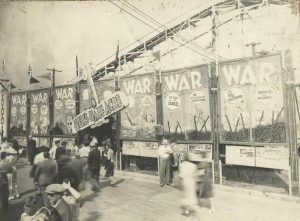 Black and white photo of carnival midway with large painted banners with war written all over, people are crowded around the entrance which has a swinging sign over it that reads Hell's Half Acre