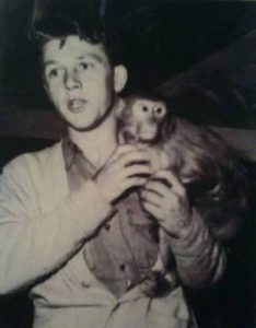 Black and white photo of young Bingo Hauser holding a monkey