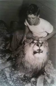 Black and white photo of young Bingo Hauser sitting by his lion, grabbing his mane and tilting his head up slightly
