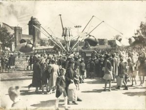 Black and white photo of a large spinning carnival ride at a midway, Flying Scooters can be partially seen