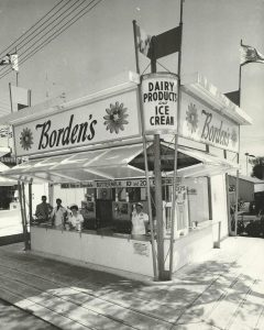 Black and white photo of Borden's ice cream stand, employees are inside with girls in all white uniforms, a sign is visible advertising for butter milk and white or chocolate milk