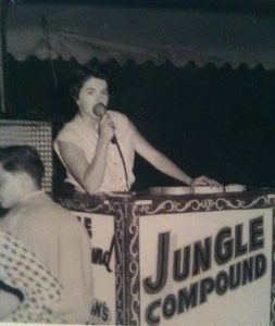 Black and white photo of a woman holding a microphone to her mouth standing behind a podium that says Jungle Compound