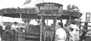 Black and white photo of a few people gathered around a kiddie ride, sign for ride reads Jimmie's Auto Ride, there is also a sign that says Special Kiddies Day five cents