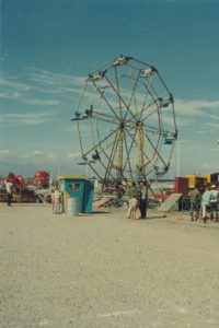 Carnival midway featuring a 12 bucket small Ferris wheel, a ticket sales box and tilt a whirl ride can also be seen