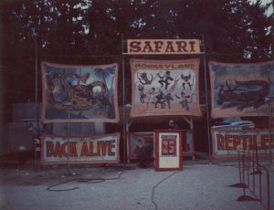 A carnival sideshow entrance for an exotic animal show, title reads Safari, there are painted banners depicting several kinds of exotic animals, and admission is advertised as 25 cents