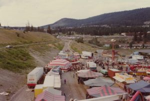 A carnival midway with many tents, rides and concessions stands, a transport truck with WCA on it can be seen, there is also a Loop-O-Plane ride visible, the background is a mountainous area with many trees