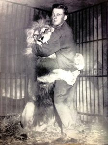 Black and white photo of young Bingo Hauser with lion Simba, both standing upright, Simba has his paws wrapped around Bingo and his mouth around his arm with a couple of sharp teeth showing