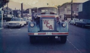 An old fashioned style truck with the letters WCA at the front, driving down a road