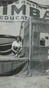 Black and white photo of a woman handling a monkey in front of a banner that says Presenting Simba, a ticket sales box is beside her