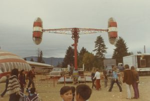 A Loop-O-Plane ride at a carnival midway, a spinning ride with one large passenger bucket each side, set up like a pendulum