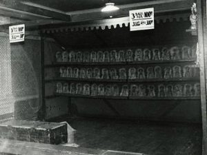 Black and white photo of a carnival cat rack game, a metal rectangular stand with three racks of clowns that can be knocked down, there is a sign that says three balls for one dollar and three cats three dollars