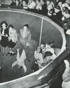 Black and white photo of a large spinning ride, people are stuck to the walls inside the large hallow dome from the acceleration, many people are above looking down to watch