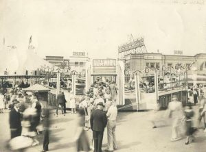 Black and white photo of crowds of people at a carnival midway, featuring people riding a Tilt-a-Whirl ride