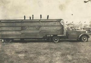 Black and white photo of a large transport vehicle with a portable generator attached, exterior advertises Conklin Shows, carnival banners can be seen in the distance
